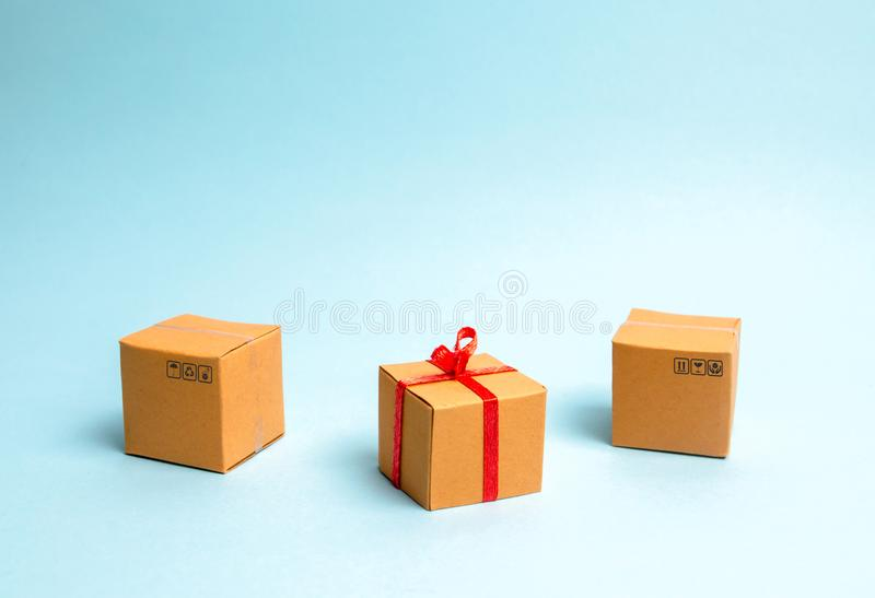 Un boîte-cadeau se trouve entre d'autres boîtes Le concept de vendre des biens et des services, cadeaux de achat pour l'anniversa photo libre de droits
