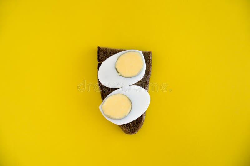 Un bocadillo de las mentiras del pan de centeno y del huevo hervido en un fondo amarillo Desayuno para la dieta Tostada con el de foto de archivo libre de regalías