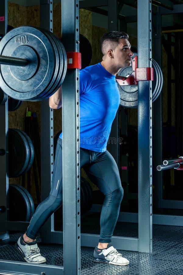 Un bodybuilder avec un barbell dans le gymnase pendant photographie stock