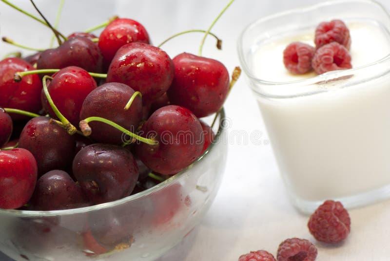 Un bol de cerises et de yaourt avec la framboise image stock