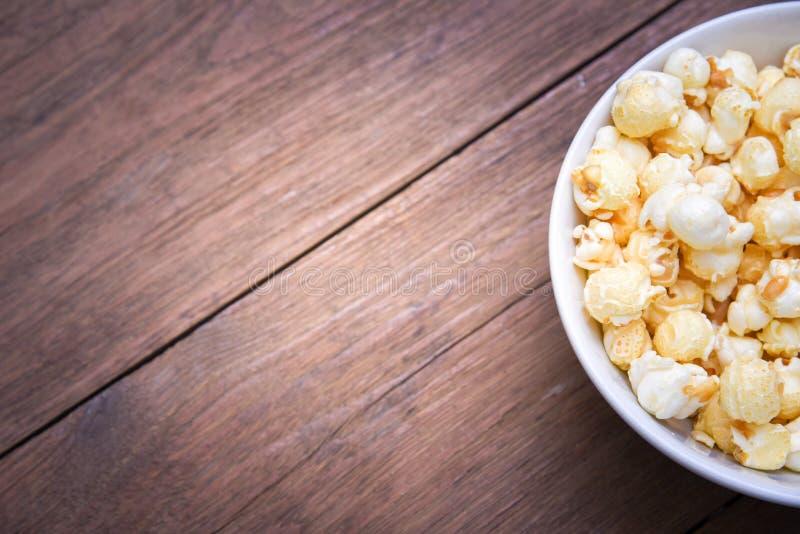 Un bol de maïs éclaté sur une table en bois photographie stock