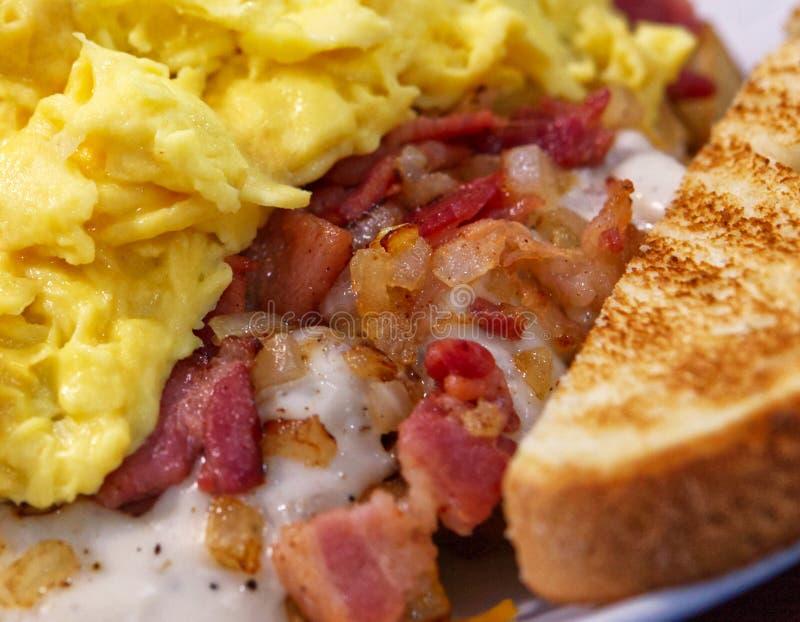 Un bol de petit déjeuner avec les pommes de terre, le lard, la sauce au jus, les oignons, les oeufs brouillés et le pain grillé images libres de droits