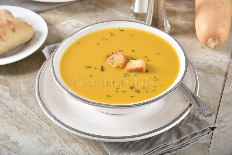 Un bol de soupe à courge de butternut avec un petit pain de dîner photos stock