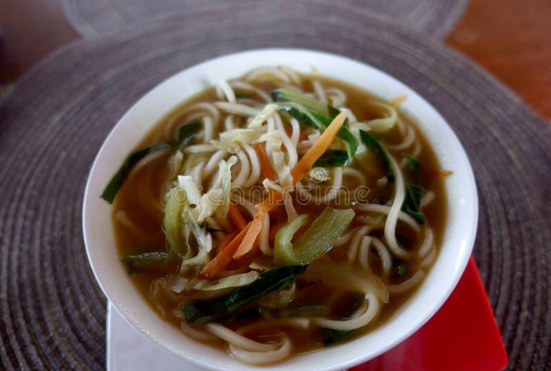 Un bol de soupe avec des nouilles et des légumes sur une serviette ronde photographie stock libre de droits