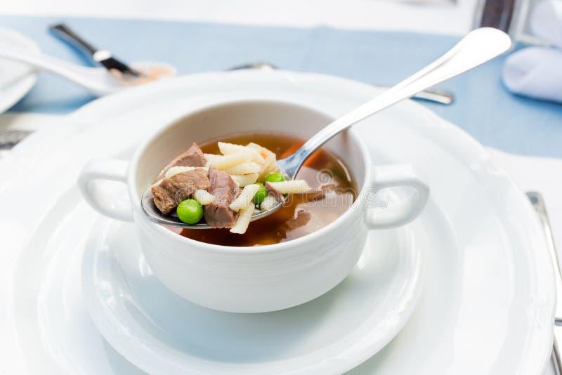 Un bol de soupe délicieuse à boeuf et à orge avec les carottes, la tomate, la pomme de terre, le céleri, et les pois images libres de droits