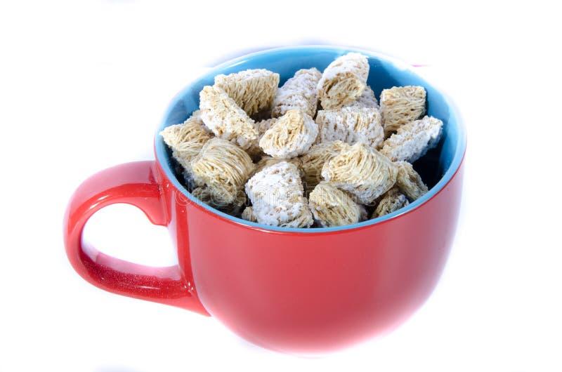 Un bol rouge et bleu de blé prêt de céréale image stock