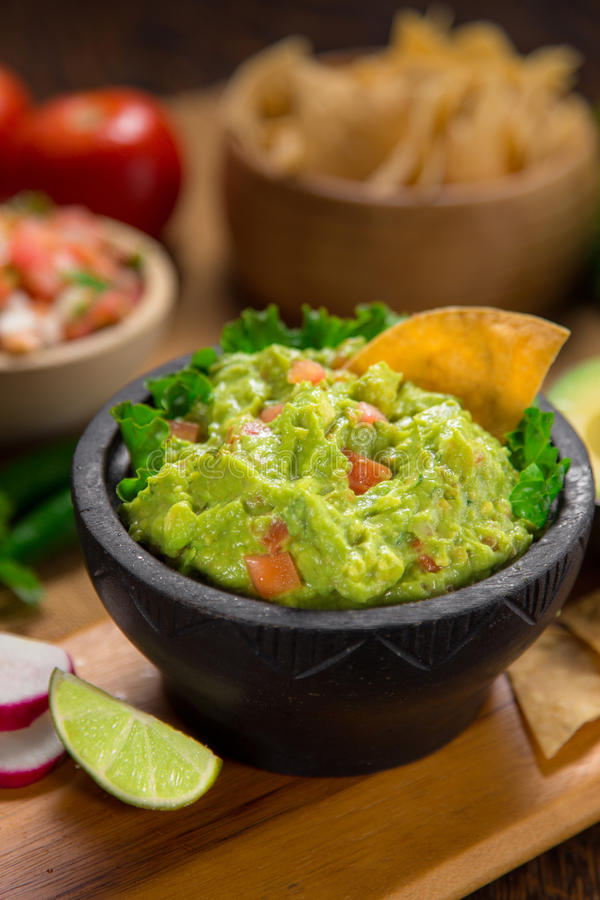Un bol vertical délicieux de tir de guacamole à côté des ingrédients frais sur une table avec les frites et le Salsa de tortilla photos libres de droits