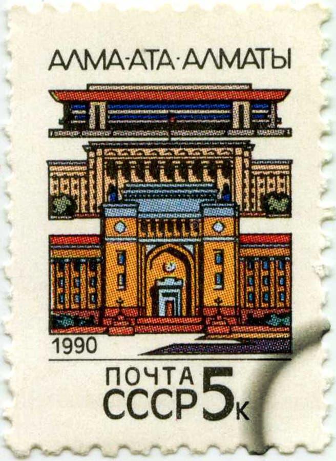 Un bollo stampato in URSS che mostra città Almaty, circa 1990 immagine stock libera da diritti
