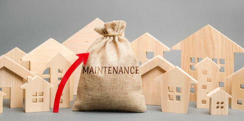 Un bolso con el mantenimiento de la palabra, las casas de madera y para arriba la flecha Precios crecientes para el mantenimiento foto de archivo