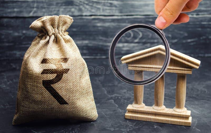 Un bolso con el rupia de la rupia india y un edificio del gobierno Volumen de ventas del dinero Depósitos, inversión y préstamo C fotografía de archivo