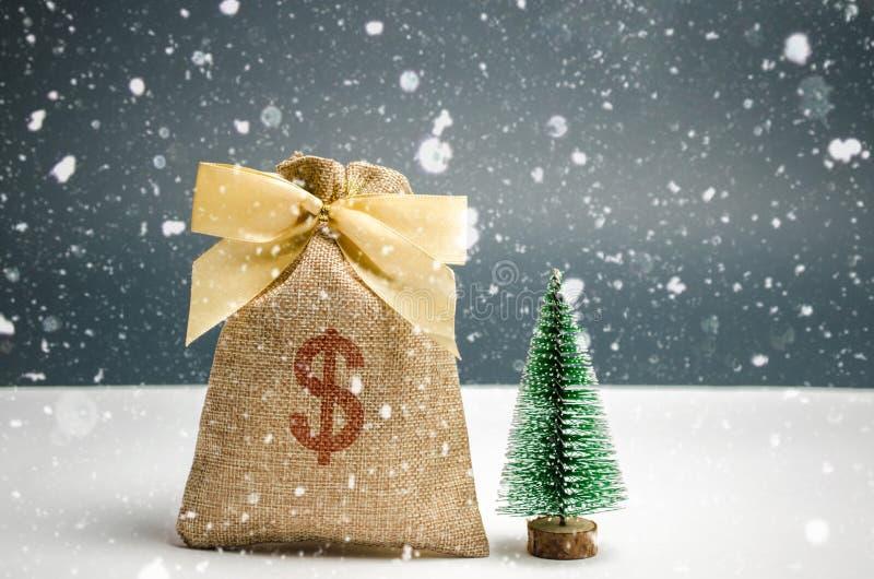 Un bolso de la muestra del dinero y de dólar con el árbol de navidad Compras de la Navidad y preparación para el día de fiesta La foto de archivo libre de regalías