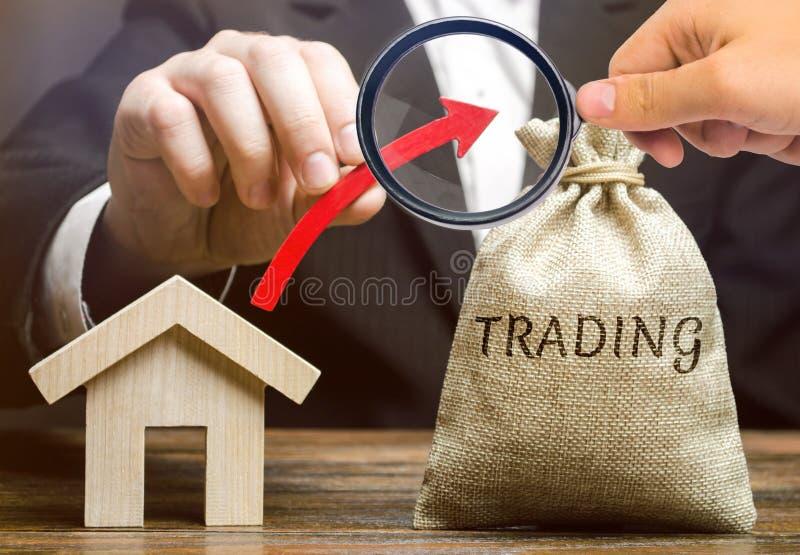Un bolso del dinero con el comercio de la palabra, una flecha ascendente y una casa de madera El concepto de aumentar la demanda  fotografía de archivo