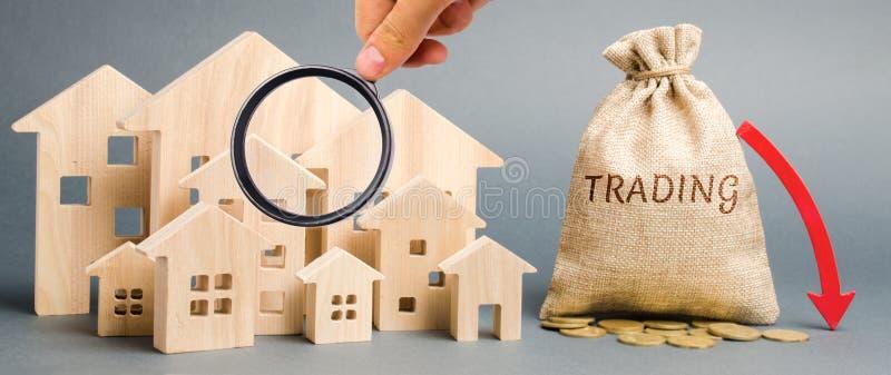 Un bolso del dinero con el comercio de la palabra, una flecha del plumón y las casas de madera El concepto de demanda decreciente fotografía de archivo