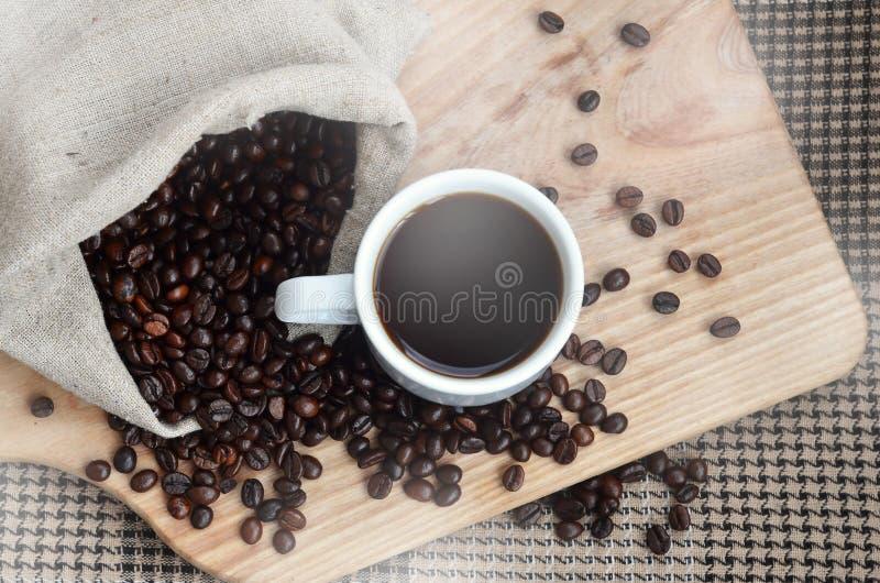 Un bolso lleno de granos de café marrones y de una taza blanca del café caliente l fotos de archivo libres de regalías