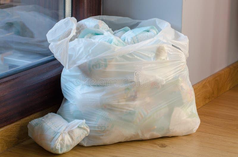 Un bolso por completo de los pañales sucios del ` s del bebé que se colocan en el piso imagenes de archivo
