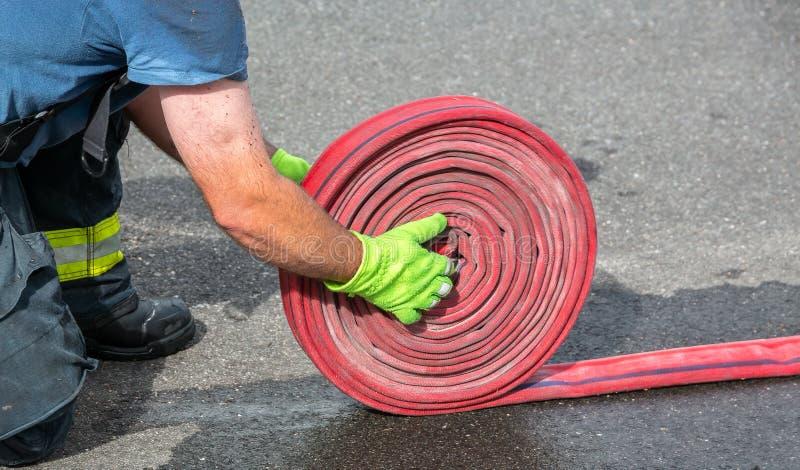 Un bombero que muestra la técnica de acumular manguera de incendios después de un incendio fotografía de archivo libre de regalías