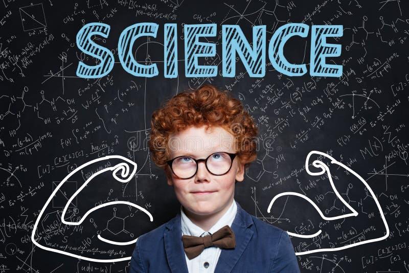 Un bon écolier aux cheveux de gingembre en science Apprendre le concept de puissance scientifique photo stock