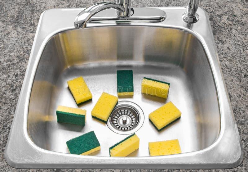 Un bon nombre d'éponges jaunes dans un bassin de cuisine propre photos stock
