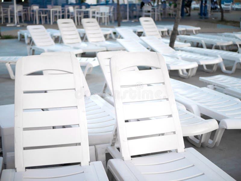 Un bon nombre de canapés vides blancs du soleil au plan rapproché de piscine au coucher du soleil photos stock