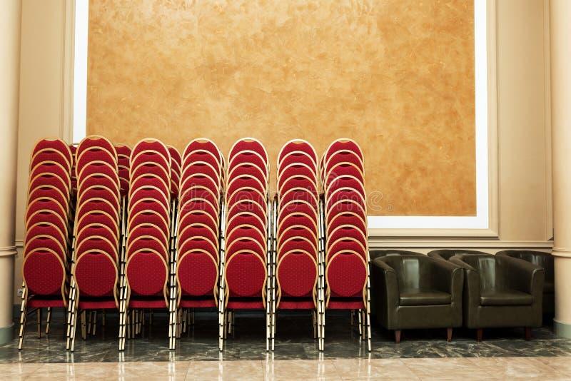Un bon nombre de chaises pliées au mur dans le hall de banquet images stock