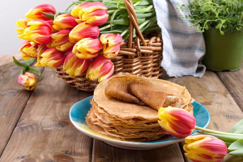 Un bon nombre de cr?pes minces sur un fond ou une table en bois, et un panier avec les tulipes rouge-jaunes fra?ches La cuisson e image libre de droits