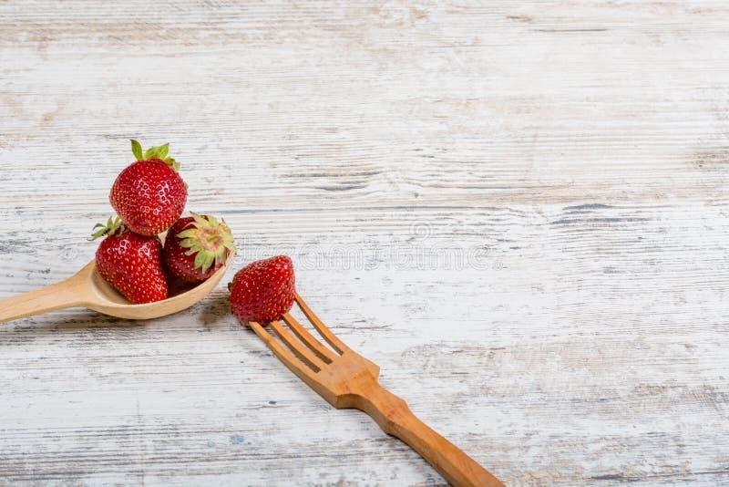 Un bon nombre de fraises parfumées mûres fraîches et une cuillère et une fourchette en bois images libres de droits