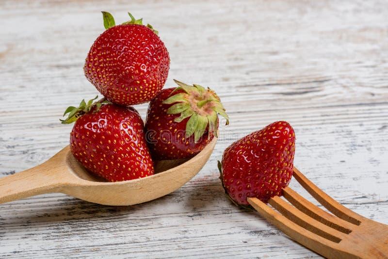 Un bon nombre de fraises parfumées mûres fraîches et une cuillère et une fourchette en bois image stock