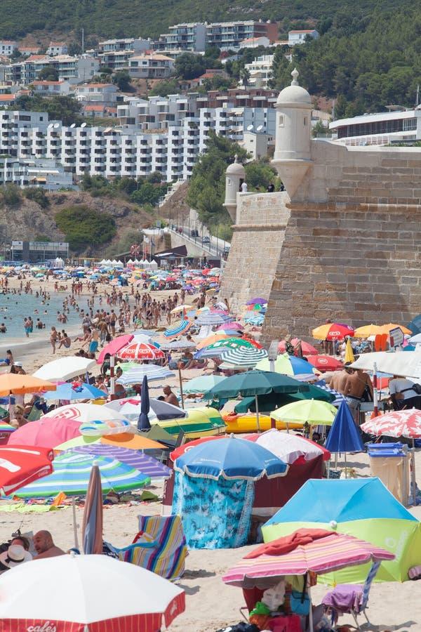 Un bon nombre de gens appréciant un jour merveilleux à la plage dans Sesimbra, Portugal photographie stock