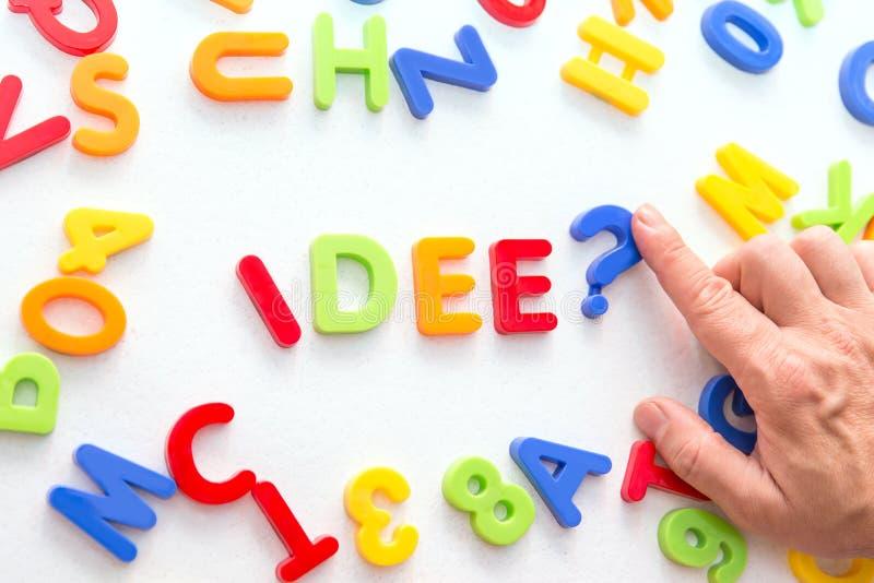 Un bon nombre de lettres colorées sur une table, main formant l'idee allemand de mot, idée photographie stock