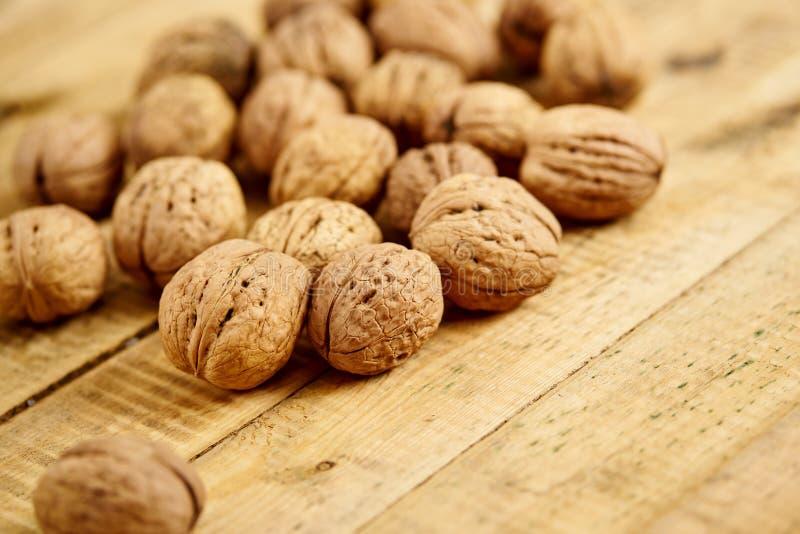Un bon nombre de noix délicieuses et fraîches sur une table en bois image stock