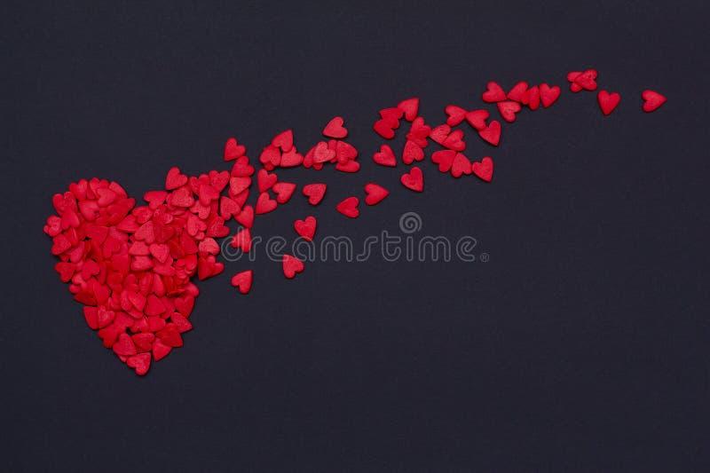 Un bon nombre de petits coeurs rouges volant sur le fond noir photo stock