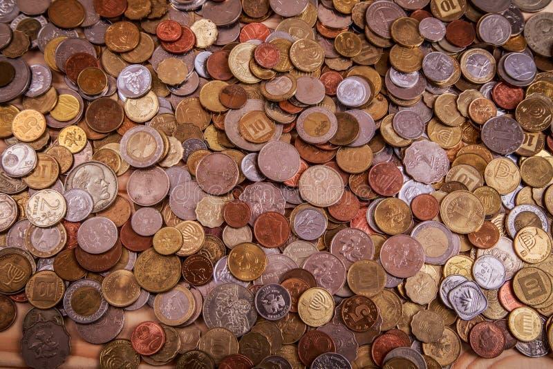 Un bon nombre de pièces de monnaie se trouvant autour du portefeuille en cuir images stock