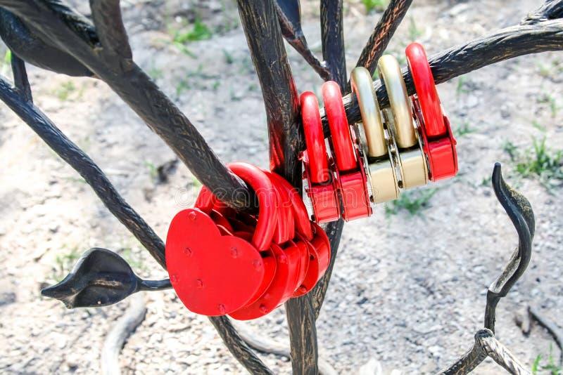 Un bon nombre de serrures en forme de coeur rouges et d'or accrochant sur un arbre en métal image stock