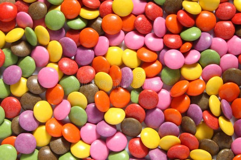 Un bon nombre de smarties colorés. image stock