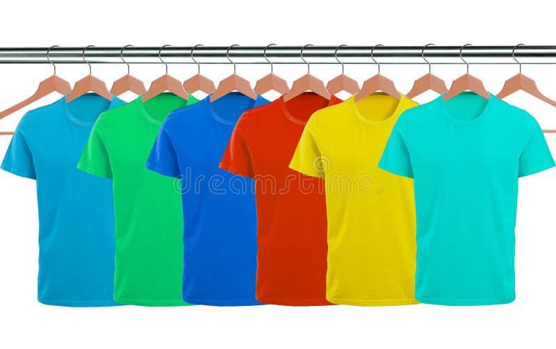 Un bon nombre de T-shirts sur des cintres d'isolement sur le blanc photographie stock libre de droits