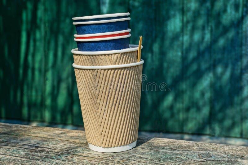 Un bon nombre de tasses de café de papier vides sur un conseil en bois gris contre un mur vert photographie stock libre de droits