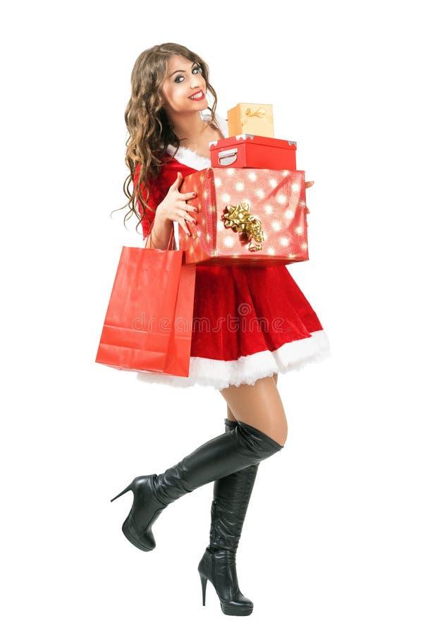 Un bon nombre de transport de belle femme enthousiaste heureuse de Santa Claus de marche de cadeaux de Noël image libre de droits