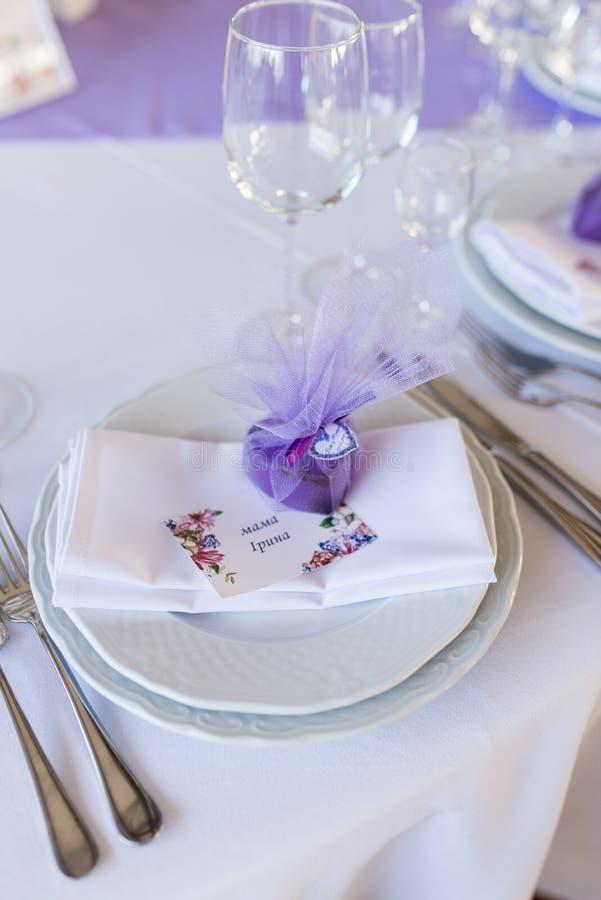 Un bonbonniere púrpura de la boda en una forma del corazón que miente en una placa blanca imágenes de archivo libres de regalías