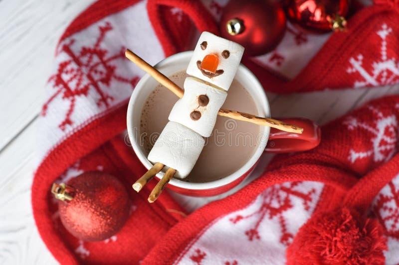 Un bonhomme de neige fait main de guimauve sur une tasse rouge avec du cacao photo stock