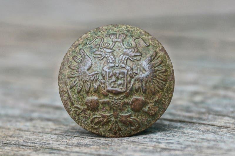 Un botón de cobre amarillo viejo con el emblema y águila en una tabla gris fotos de archivo