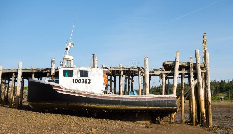 Un bote de langosta atado a un espigón con marea baja en la marisma imágenes de archivo libres de regalías