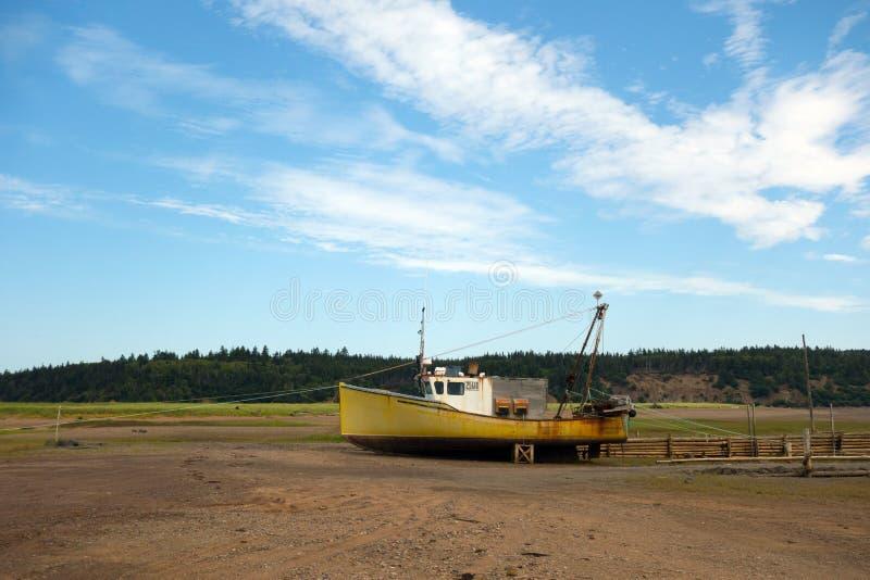 Un bote de langosta atado a un espigón con marea baja en la marisma foto de archivo