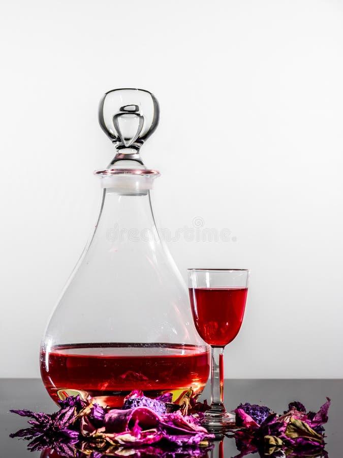 Un bottiglione alla moda, un bicchiere di vino & alcuni petali rosa fotografia stock libera da diritti