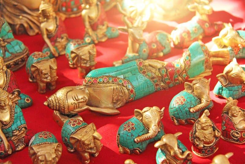Un Bouddha étendu a fait du bronze sur un fond rouge et d'autres figures pour une présentation de cadeau à partir de l'Inde image libre de droits