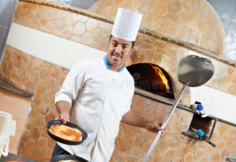 Chef arabe de boulanger faisant la pizza image stock