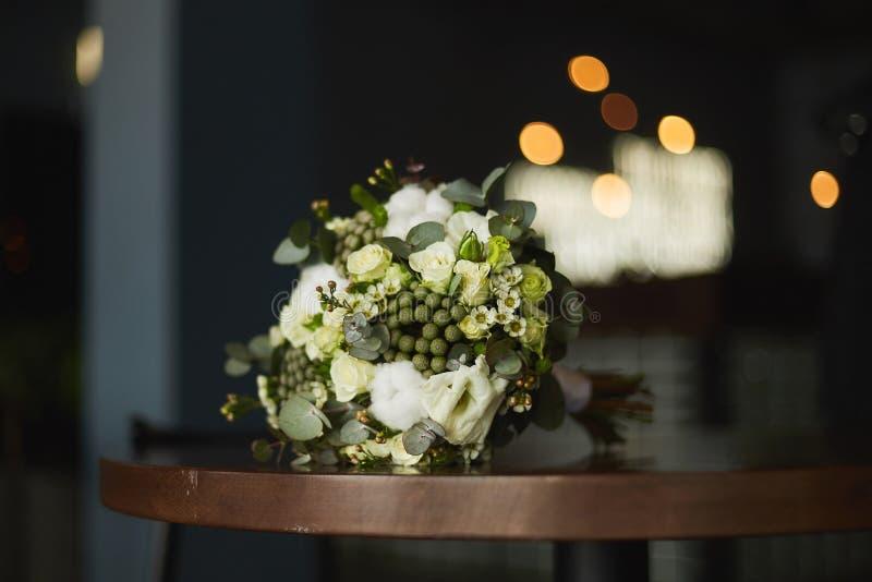 Un bouquet élégant des fleurs avec les roses blanches et jaunes attachées avec un ruban se trouve sur une table image libre de droits