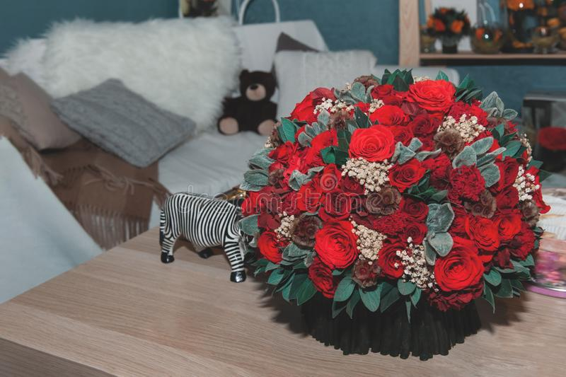 Un bouquet énorme des roses rouges est décoré dans l'intérieur sur une table en bois photographie stock