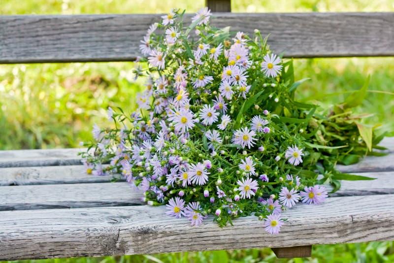 Un bouquet d'automne fleurit sur un banc en bois photos stock
