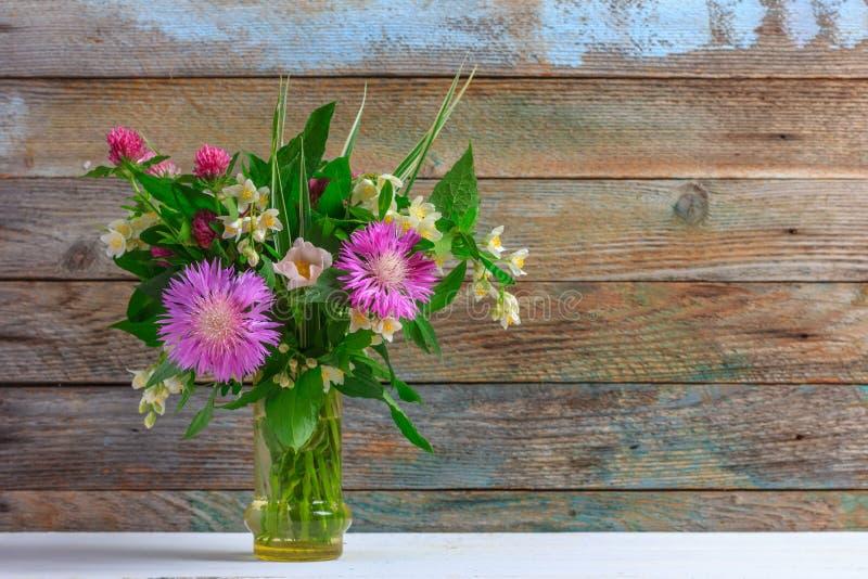 Un bouquet des fleurs du trèfle, des bleuets et du jasmin dans un vase en verre sur une table en bois blanche sur un rétro fond g image libre de droits