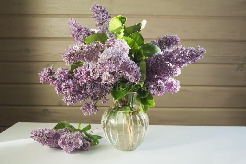 Un bouquet des lilas frais dans un beau vase en verre sur une table blanche dans une ferme image libre de droits